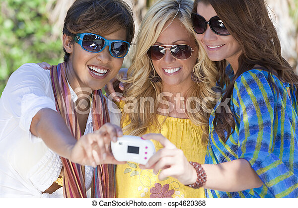 Three beautiful young women in their twenties laughing and having fun taking pictures of themselves using a digital camera while on vacation in a tropical resort location. - csp4620368