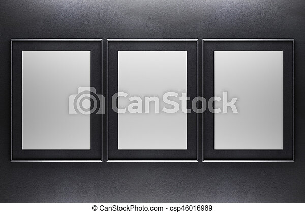 Three blank frames. Three blank picture frames on dark concrete ...