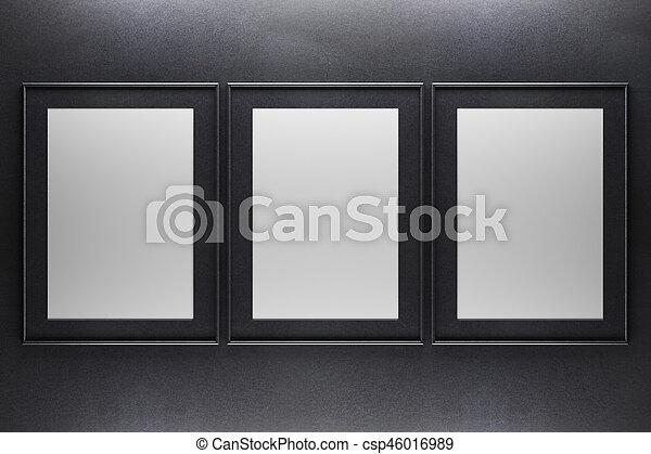 Three blank frames. Three blank picture frames on dark concrete ...