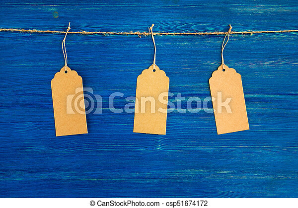 Three brown blank paper price tags or labels set hanging on a rope on the blue wooden background. - csp51674172