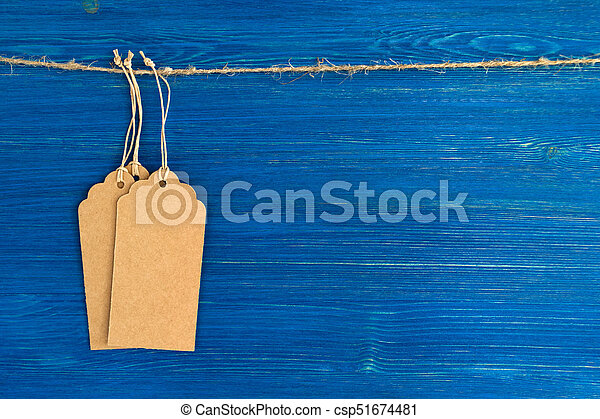 Three brown blank paper price tags or labels set hanging on a rope on the blue wooden background. - csp51674481