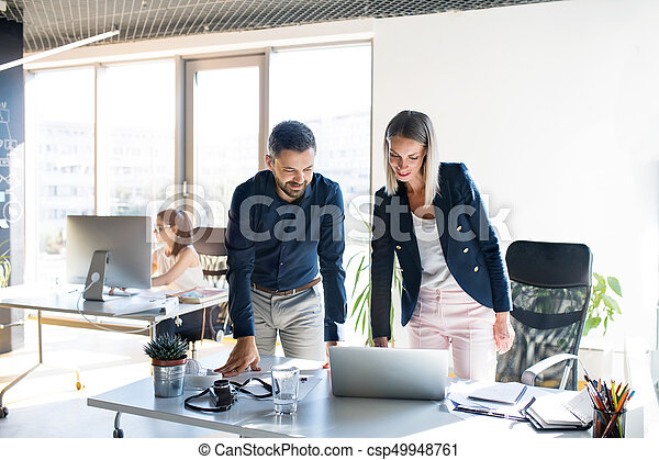 Three business people in the office working together. - csp49948761