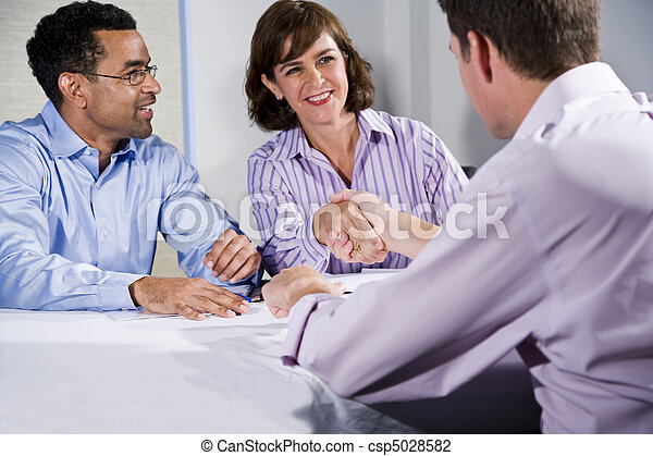 Three business people meeting, men shaking hands - csp5028582