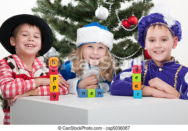 """Three children dressed in carnival suits are greeting with sigh """"happy new year"""" made with blocks at the decorated christmas tree; isolated on the white background - csp5036087"""