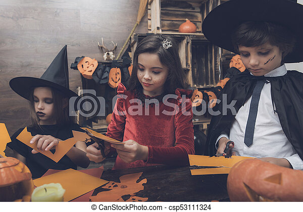 Three children in costumes of fairy-tale monsters on Halloween cut out bats  from paper