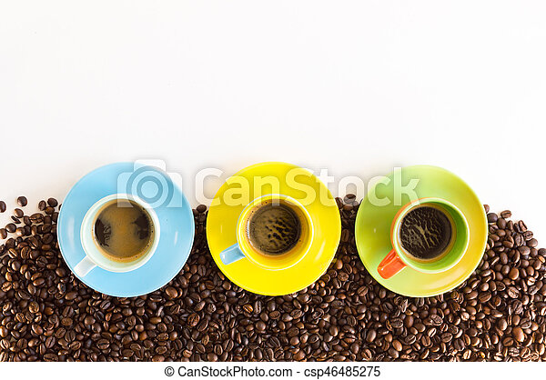three colorful coffee cups on group of coffee beans colorful coffee