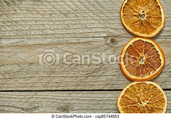 three dried orange slices on wooden background, top view, copy space - csp85744853