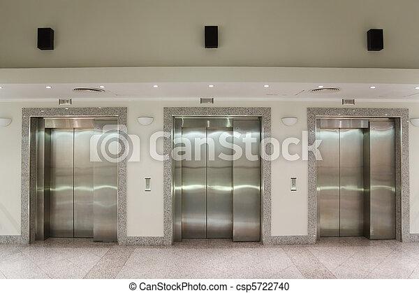 Three elevator doors in corridor of office building - csp5722740