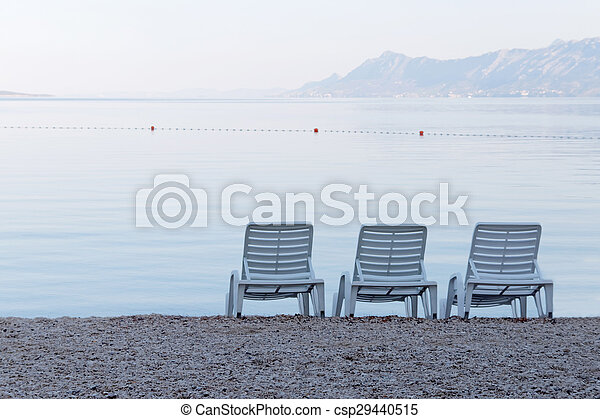 Three empty deck chair on the beach - csp29440515
