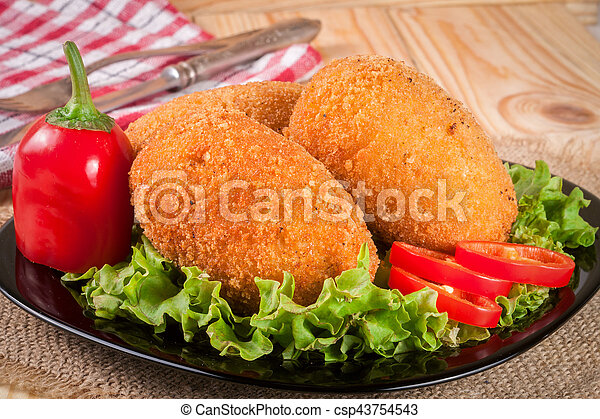 three fried breaded cutlet with lettuce on a black plate and wooden background - csp43754543