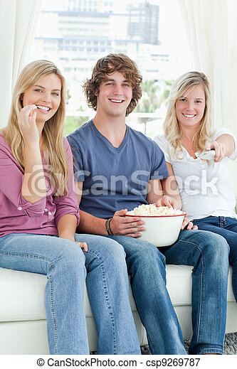 Three friends eating popcorn while smiling and using the tv remote to change the channel - csp9269787