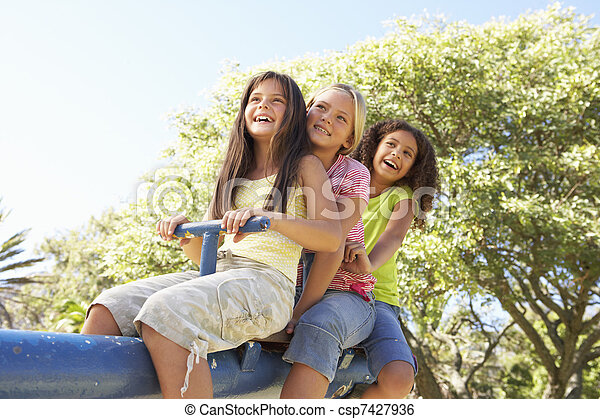 Three Girls Riding On See Saw In Playground - csp7427936