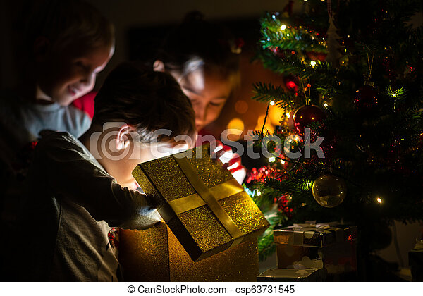 Three kids, two toddler boys and a girl, opening a golden gift box - csp63731545