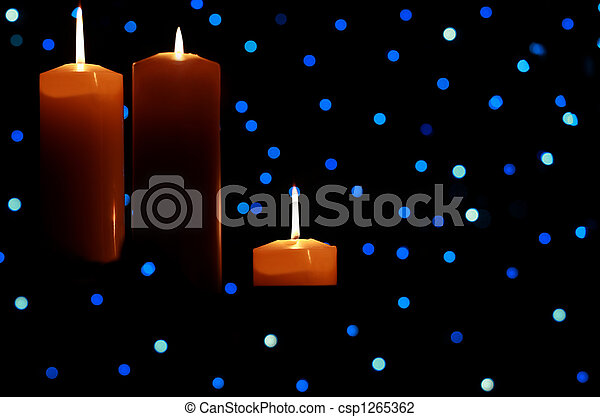 Three large candles lit amongst blue lights - csp1265362