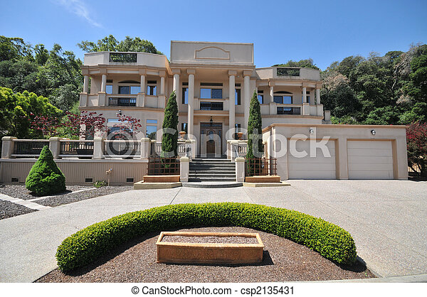 Three Level House With Semi Circle Hedge In Front And Circular Driveway Two Garage Doors Steps To Front Door