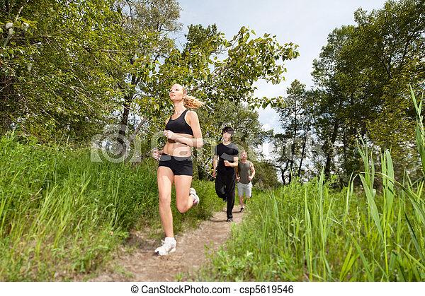 Three people running on pathway - csp5619546