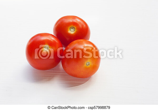 Three red tomatoes on a white . - csp57998879