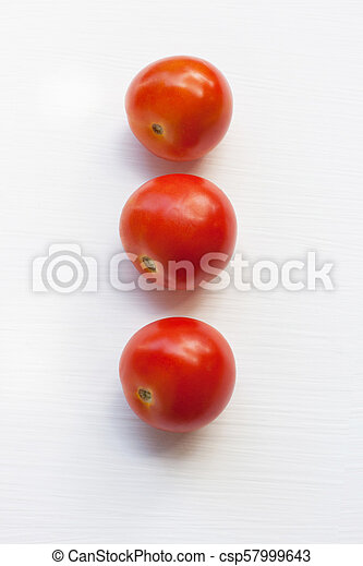 Three red tomatoes on a white . - csp57999643