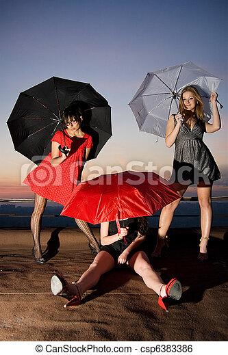 Three sexy chicks with umbrellas posing on the roof - csp6383386