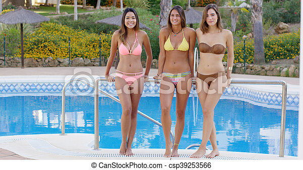 Three shapely sexy women in bikinis poolside - csp39253566