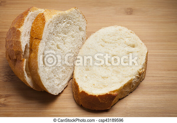 Three slices of French Bread on wooden cutting board. - csp43189596