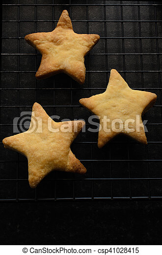 Three Star Shaped Christmas Biscuits On Cooling Rack