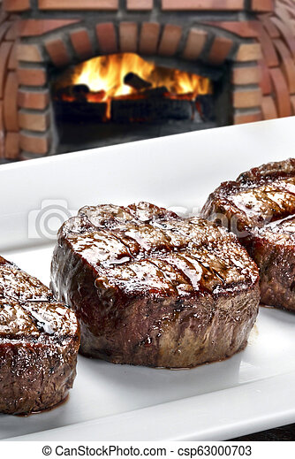 Three steaks roasted on the grill - csp63000703