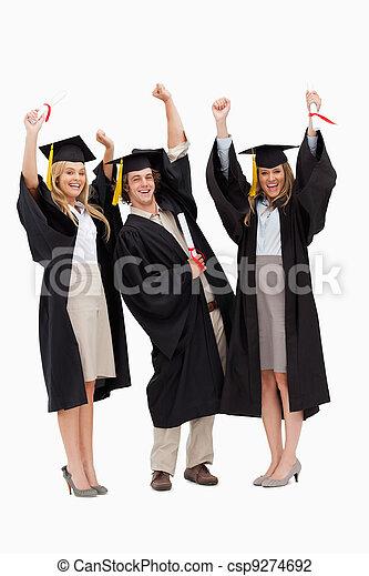 Three students in graduate robe raising their arms - csp9274692