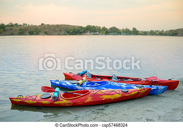 Three Traveling Kayaks on the Sand Beach near Beautiful River or Lake at the Evening. Travel and Adventure Concept. - csp57468324