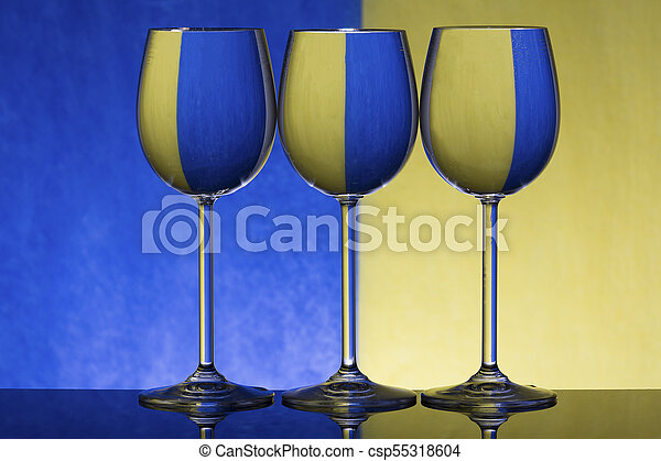 Three wineglasses on a shiny surface with water that distort yellow and blue background - csp55318604