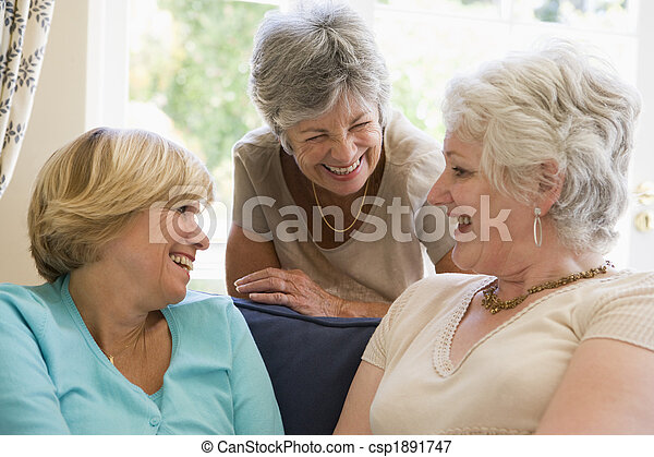Three women in living room talking and smiling - csp1891747