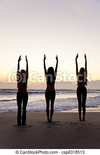 Three Women Practicing Yoga on Beach At Sunrise or Sunset - csp6318513