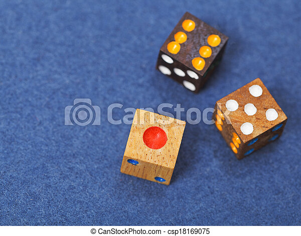 three wooden gambling dices on blue cloth - csp18169075