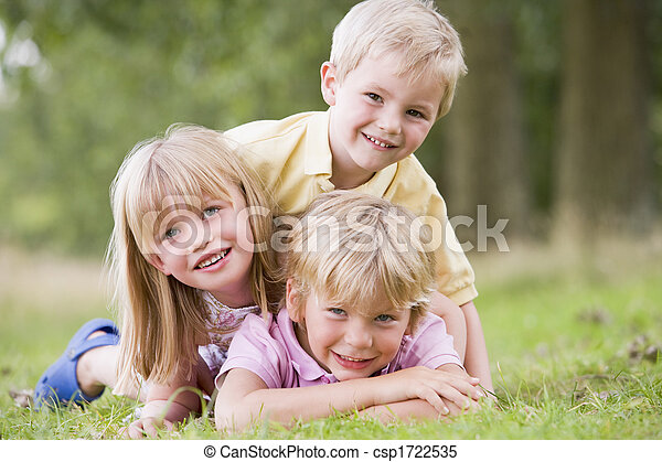 Three young children playing outdoors smiling - csp1722535