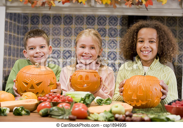 Three young friends on Halloween with jack o lanterns and food s - csp1894935