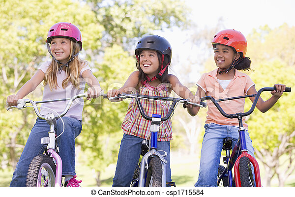 Three young girl friends outdoors on bicycles smiling - csp1715584