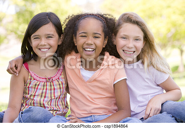 Three young girl friends sitting outdoors smiling - csp1894864