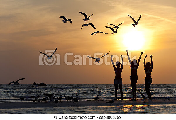 Three Young Women Dancing On Beach At Sunset - csp3868799