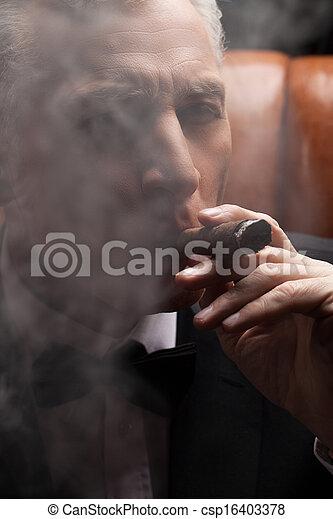 Through a cigar smoke. Close-up of confident mature man smoking a cigar - csp16403378