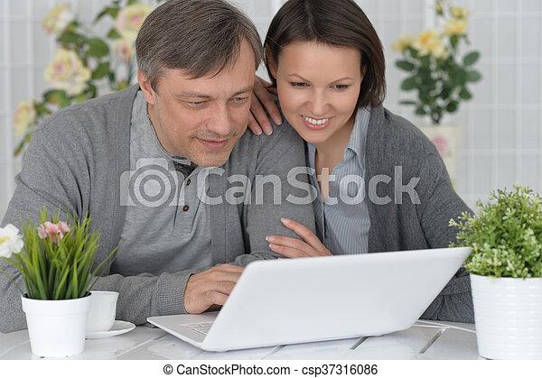 thuis, paar, vrolijke , draagbare computer, gebruik - csp37316086