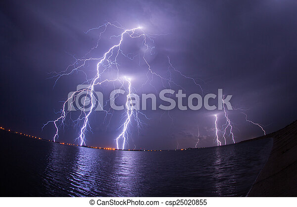 Thunderstorm and lightnings in night over a lake with reflaction - csp25020855