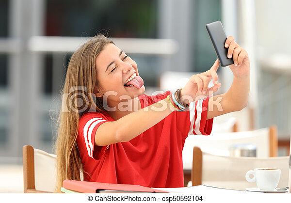 Estudiante tomando selfie en una cafetería - csp50592104