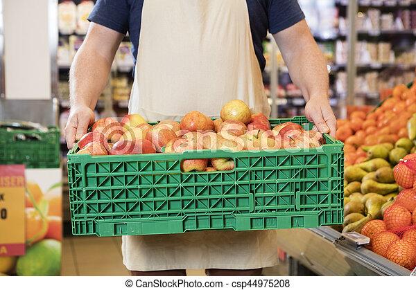 Vendedor llevando manzanas en cajas en el supermercado - csp44975208