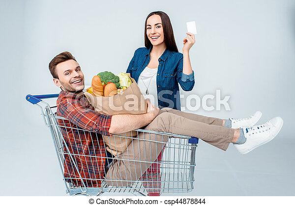 Un hombre sentado en un carrito de supermercado con una