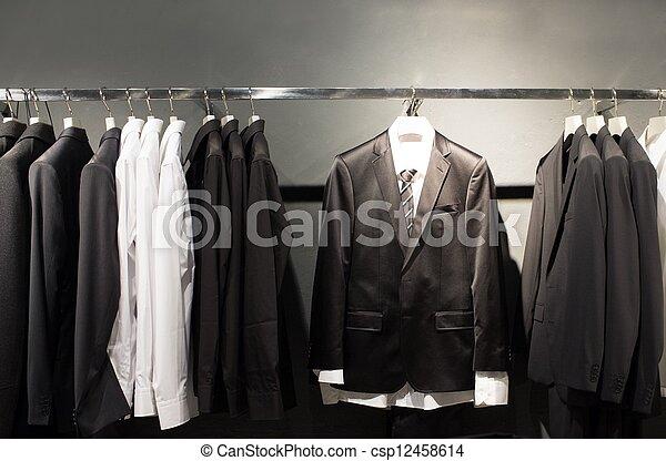 Fila de trajes en la tienda - csp12458614
