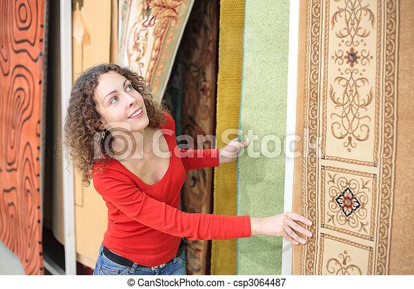 Una joven en la tienda con alfombras - csp3064487