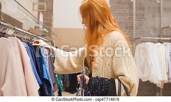 La mujer elige el vestido en la tienda - csp47714619