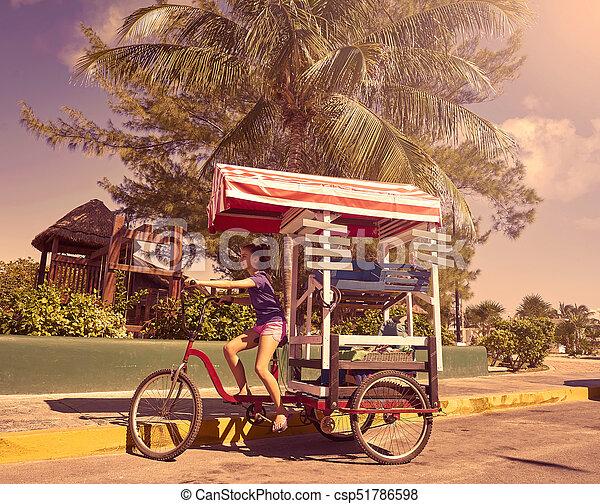 Una chica joven con una tienda de triciclos caribeños - csp51786598