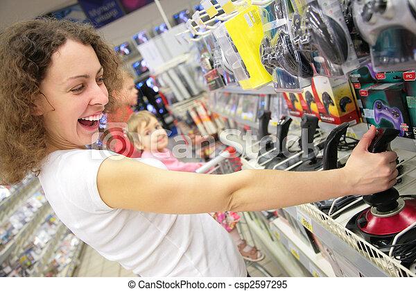 La joven de la tienda juega con joystick - csp2597295