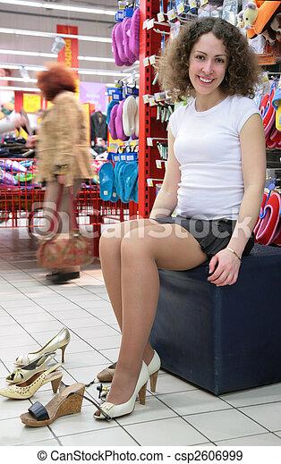 Una joven con zapatos en la tienda - csp2606999